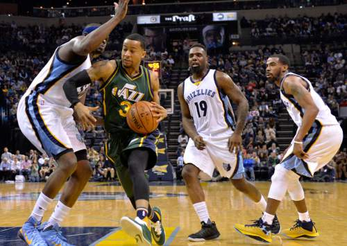 Utah Jazz guard Trey Burke (3) drives against Memphis Grizzlies forward Zach Randolph, left, forward P.J. Hairston (19) and guard Mike Conley, right, during the second half of an NBA basketball game Friday, March 4, 2016, in Memphis, Tenn. (AP Photo/Brandon Dill)