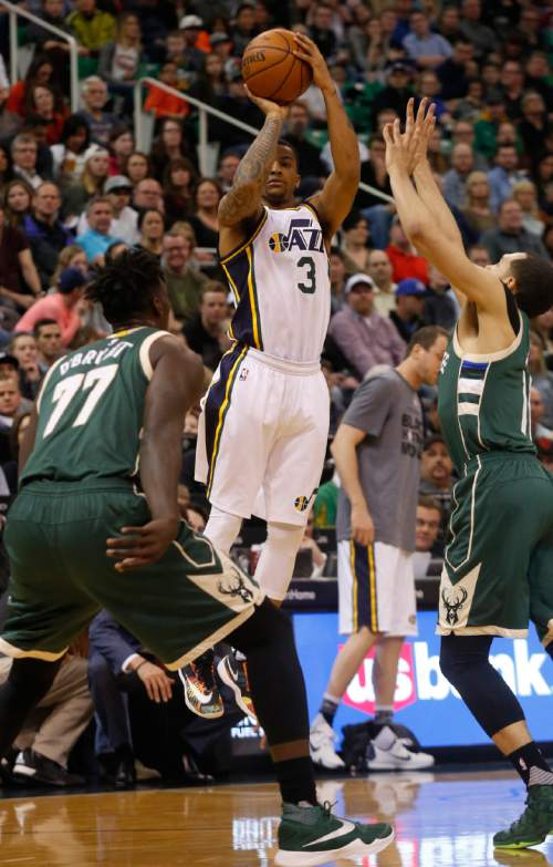 Utah Jazz's Trey Burke (3) shoots the ball as Milwaukee Bucks' Johnny O'Bryant (77) and Milwaukee Bucks' Tyler Ennis, right, defend during the first half of an NBA basketball game Friday, Feb. 5, 2016, in Salt Lake City. (AP Photo/Kim Raff)