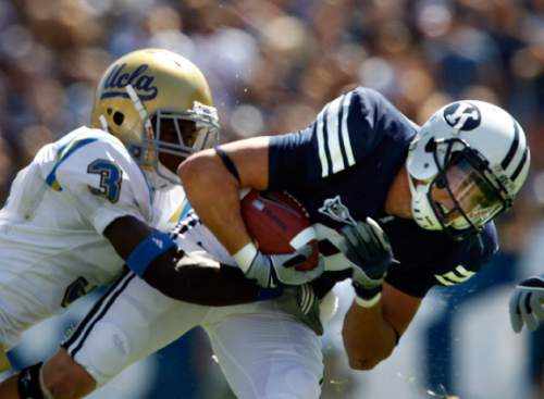 Rick Egan  |  The Salt Lake Tribune   Austin Collie, (8) BYU, struggles for some extra yards as UCLA  Defensive Back Rahim Moore (3) grabs him,  after catching a pass, in football action, BYU vs UCLA at Lavell Edwards Stadium in Provo.  The Cougars shut out the Bruins 59-0 Saturday, September 13, 2008.