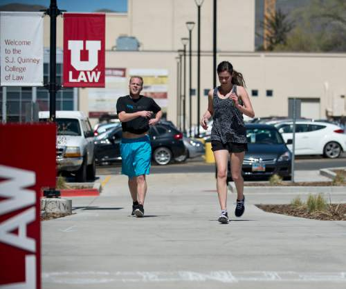 Lennie Mahler     The Salt Lake Tribune  University of Utah law students Scott Manning and Brooke Parrish cross the finish line of a mile route around campus Thursday, April 7, 2016. Law students and faculty worked to accumulate a total of 100 miles before law school dean Robert Adler runs a 100-mile course in Zion National Park on Friday. Adler will run the ultra-marathon to push for a 100% bar exam passage rate and 100% employment for law graduates.