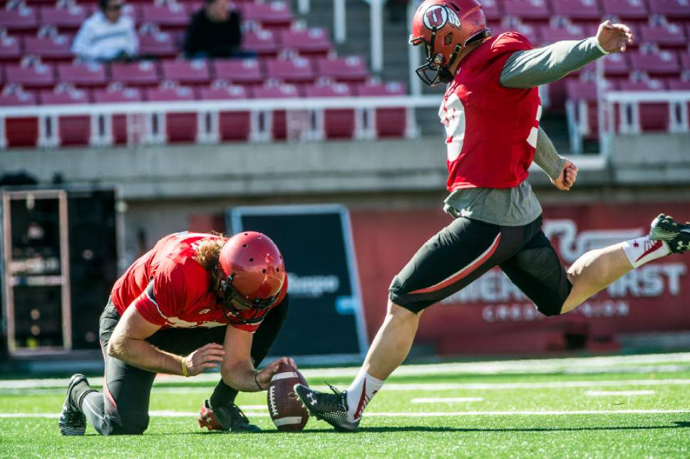 Chris Detrick  |  The Salt Lake Tribune Utes punter Mitch Wishnowsky (33) holds the ball as Andy Phillips (39) kicks a field goal during a practice at Rice-Eccles Stadium Tuesday April 5, 2016.