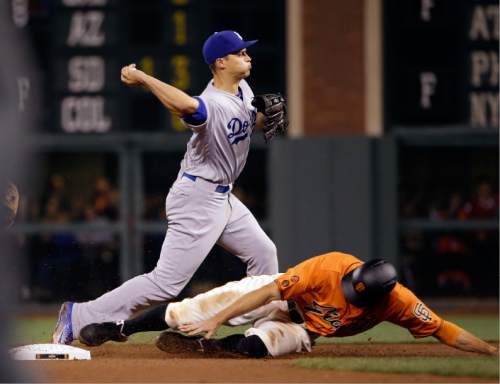 Los Angeles Dodgers shortstop Corey Seager throws to first after forcing out San Francisco Giants' Hunter Pence at second base on a ground ball by Brandon Belt during the seventh inning of a baseball game Friday, April 8, 2016, in San Francisco. Belt was safe at first base. (AP Photo/Marcio Jose Sanchez)