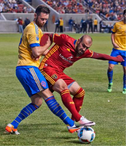 Michael Mangum  |  Special to the Tribune  Real Salt Lake forward Yura Movsisyan (14) battles for possession with pressure from Colorado Rapids defender Bobby Burling (23) during the second half their match at Rio Tinto Stadium in Sandy, UT on Saturday, April 9, 2016. RSL won 1-0.