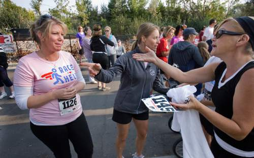 "Scott Sommerdorf  |  The Salt Lake Tribune  Meri Brown, left, from the TV program ""Sister Wives"" carries on a conversation with a friend near the starting line of the 5K run to benefit Holding Out Help, a group that helps people leaving polygamy. The run started at 9 a.m. from Draper City Park, Saturday, September 22, 2012."
