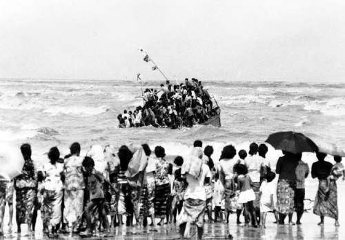 Vietnamese refugees getting down from a sinking boat which they brought in to the Kuala Terengganu beach, Malaysia on Sunday, Dec. 4, 1978. There were 153 on board and all were rescued. (AP Photo)