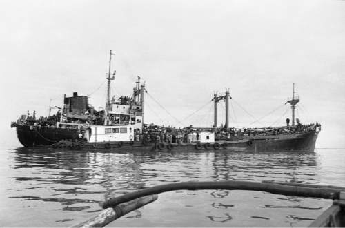 Tugboats load water onto the refugee ship Tung An at its anchorage in Manila Bay  Thursday, Dec. 28, 1978. The Philippines says the more than 2,300 Vietnamese ìboat peopleî aboard cannot go ashore. (AP Photo/AH)