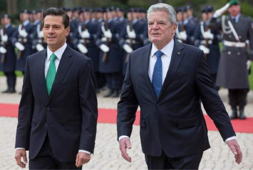German President Joachim Gauck, right, welcomes the President of Mexico Enrique Pena Nieto, left, with military honors for a meeting at the Bellevue palace in Berlin, Germany, Monday, April 11, 2016. (AP Photo/Michael Sohn)