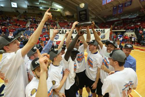 The Salt Lake Bruins celebrate with the championship trophy after winning the championship game of the NJCAA tournament 74-63 over Hutchinson Saturday, March 19, 2016, at the Sports Arena in Hutchinson, Kan. (Travis Morisse/The Hutchinson News via AP ) MANDATORY CREDIT