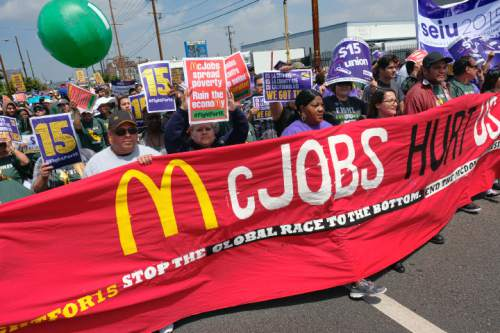 Protesters march to a McDonald's restaurant in downtown Los Angeles on Thursday, April 14, 2016. Protesters calling for pay of $15 an hour and a union were at McDonald's restaurants around the country and overseas Thursday as part of an ongoing push targeting the world's biggest hamburger chain. (AP Photo/Richard Vogel)