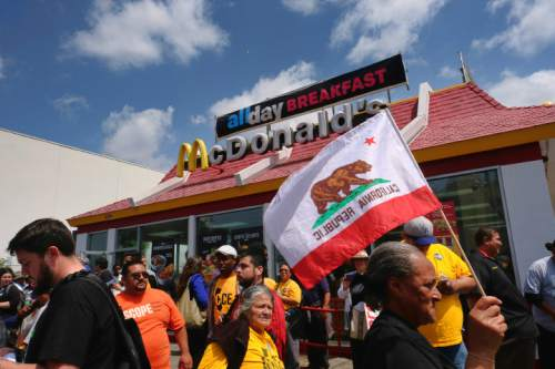 Erma Hall-Wood carries a California state flag while joining other protesters in front of a McDonald's restaurant in downtown Los Angeles on Thursday, April 14, 2016. Protesters calling for pay of $15 an hour and a union were at McDonald's restaurants around the country and overseas Thursday as part of an ongoing push targeting the world's biggest hamburger chain. (AP Photo/Richard Vogel)