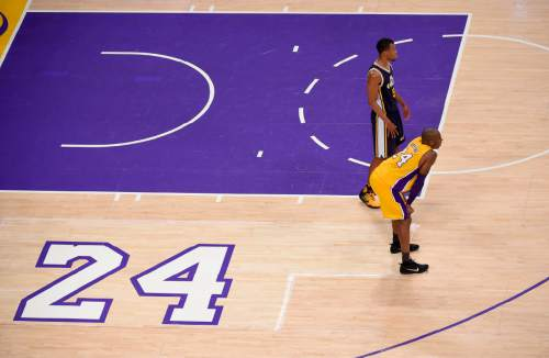Los Angeles Lakers forward Kobe Bryant, foreground, and Utah Jazz guard Rodney Hood pause during the first half of Bryant's last NBA basketball game, Wednesday, April 13, 2016, in Los Angeles. (AP Photo/Mark J. Terrill)
