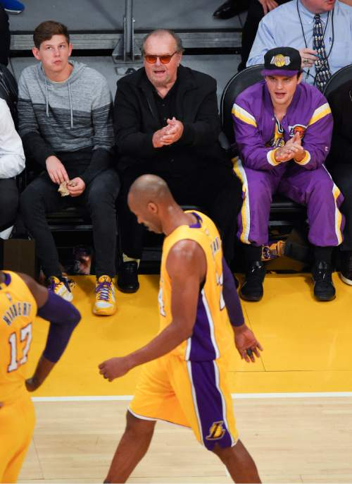 Actor Jack Nicholson, middle, claps as Los Angeles Lakers forward Kobe Bryant walks by during the first half of Bryant's last NBA basketball game, against the Utah Jazz, Wednesday, April 13, 2016, in Los Angeles. (AP Photo/Mark J. Terrill)