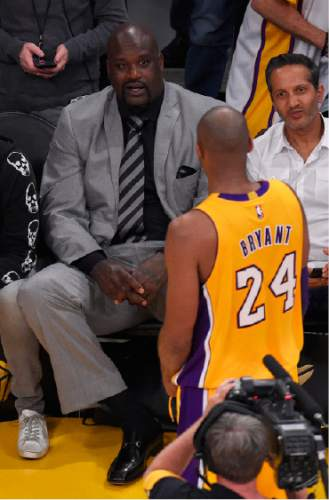 Shaquille O'Neal, left, talks with Los Angeles Lakers forward Kobe Bryant during the first half of the Lakers' NBA basketball game against the Utah Jazz, Wednesday, April 13, 2016, in Los Angeles. (AP Photo/Mark J. Terrill)