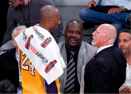 Former player Shaquille O'Neal, middle, watches as Los Angeles Lakers forward Kobe Bryant and trainer Gary Vitti talk during the first half of Bryant's last NBA basketball game, against the Utah Jazz, Wednesday, April 13, 2016, in Los Angeles. (AP Photo/Mark J. Terrill)