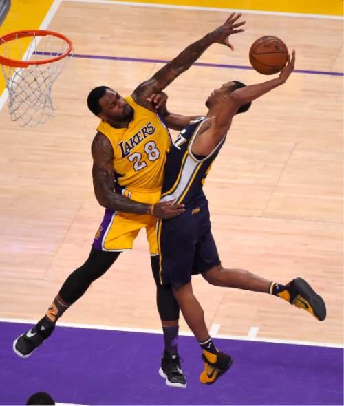 Los Angeles Lakers center Tarik Black, left, blocks the shot of Utah Jazz guard Rodney Hood during the second half of an NBA basketball game Wednesday, April 13, 2016, in Los Angeles. (AP Photo/Mark J. Terrill)