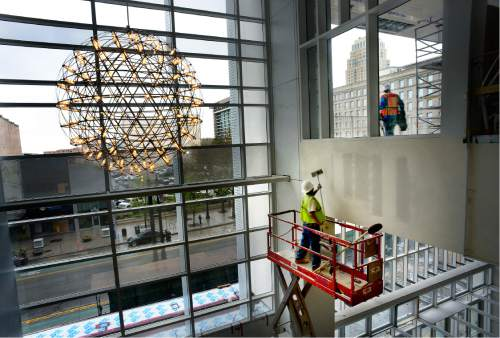 Scott Sommerdorf   |  The Salt Lake Tribune   Workers in the six-story Grand Lobby look past the recently illuminated Moooi lights onto Main Street during a tour of the construction on The George S. and Dolores Doré Eccles Theater on Thursday, April 14, 2016.