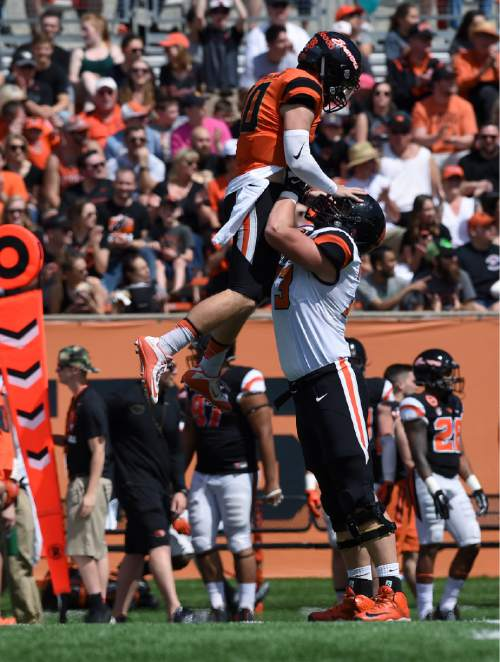 Oregon State quarterback Darell Garretson (10) is hoisted by offensive lineman Blake Brandel (73) after throwing a 43-yard touchdown during an NCAA college spring football game, on Saturday, April 16, 2016 in Corvallis, Ore. (Godofredo Vasquez/The Corvallis Gazette-Times via AP) MANDATORY CREDIT