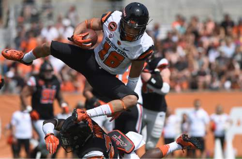 Oregon State wide receiver Paul Lucas (16) hurdles over cornerback Jay Irvine (24) during an NCAA college spring football game, on Saturday, April 16, 2016 in Corvallis, Ore. (Godofredo Vasquez/The Corvallis Gazette-Times via AP) MANDATORY CREDIT
