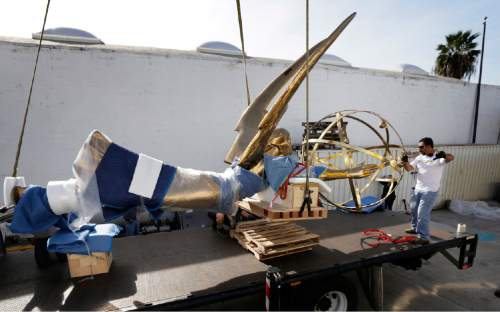 Workers prepare to offload a large replica of an Emmy statuette as it arrives at the Academy's headquarters campus in the North Hollywood district of Los Angeles Friday, April 15, 2016. The 30-foot-tall, 1,750-pound bronze statue will be installed in the Academy's redesigned Hall of Fame Plaza that will open to the public in late spring. (AP Photo/Nick Ut)