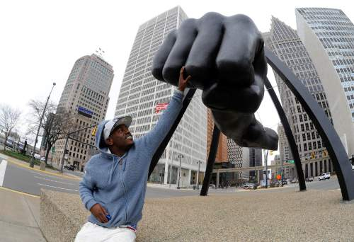 In a photo from March 28, 2016, Robert Wilcoxson stands next to The Monument to Joe Louis in Detroit. Wilcoxson is one of two people freed by the North Carolina Innocence Inquiry Commission, and he received $5 million in compensation. (AP Photo/Jose Juarez)