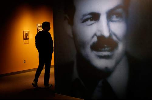 """A museum visitor, left, walks past a photograph of Ernest Hemingway in the exhibit: """"Ernest Hemingway: Between Two Wars"""" at the John F. Kennedy Presidential Library and Museum on Tuesday, April 12, 2016, in Boston. Original drafts of Ernest Hemingway works along with personal items are on display for the first time at the museum. (AP Photo/Steven Senne)"""