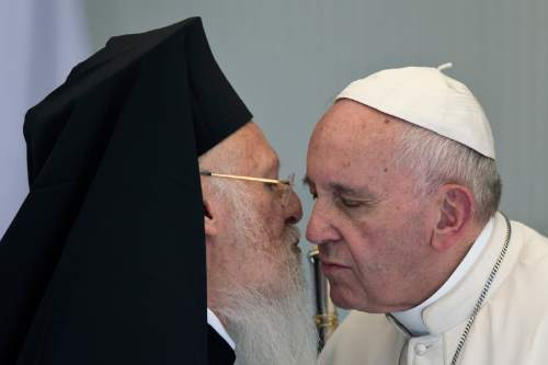 Pope Francis, right, greets Ecumenical Patriarch Bartholomew I, spiritual leader of the world's Orthodox Christians, during their joint visit to the Moria refugee detention center on the Greek island of Lesbos, Saturday April 16, 2016. Pope Francis gave Europe a concrete lesson Saturday in welcoming refugees by bringing 12 Syrian Muslims to Italy aboard his charter plane after an emotional visit to the Greek island of Lesbos, which has faced the brunt of Europe's migration crisis. (AP Photo/Petros Giannakouris)