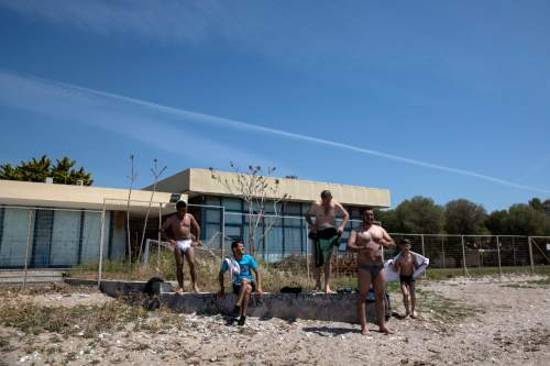 Syrians stand on a beach after swimming near the old international airport which is used as a temporary camp in Athens, on Sunday, April 17, 2016. Greek authorities, worried about the spread of diseases in makeshift camps, are urging migrants to relocate to organized camps with better living conditions.  (AP Photo/Yorgos Karahalis)