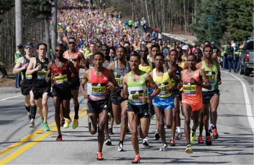Yemane Tsegay, left center, and Deribe Robi, right center, both of Ethiopia, lead the pack of runners just after the start in Hopkinton, Mass., of the 120th Boston Marathon on Monday, April 18, 2016. (AP Photo/Steven Senne)