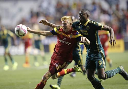 Portland Timbers' Fanendo Adi (9) battles with Real Salt Lake's Justen Glad (14) during the second half of an MLS soccer game Wednesday, Oct. 14, 2015, in Sandy, Utah. The Timbers won 1-0. (AP Photo/Rick Bowmer)