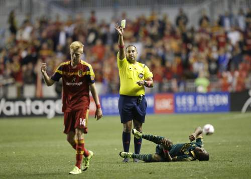Real Salt Lake's Justen Glad (14) receives a yellow card after fouling Portland Timbers' Darlington Nagbe, right, during the second half of an MLS soccer match Wednesday, Oct. 14, 2015, in Sandy, Utah. The Timbers won 1-0. (AP Photo/Rick Bowmer)