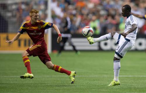 Vancouver Whitecaps' Kekuta Manneh, right, of Gambia, passes the ball over Real Salt Lake's Justen Glad during the first half of an MLS soccer game in Vancouver, British Columbia, Saturday, Aug. 8, 2015. (Darryl Dyck/The Canadian Press via AP) MANDATORY CREDIT