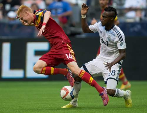 Real Salt Lake's Justen Glad, left, and Vancouver Whitecaps' Gershon Koffie, of Ghana, collide during the first half of an MLS soccer game in Vancouver, British Columbia, Saturday, May 30, 2015. (Darryl Dyck/The Canadian Press via AP) MANDATORY CREDIT