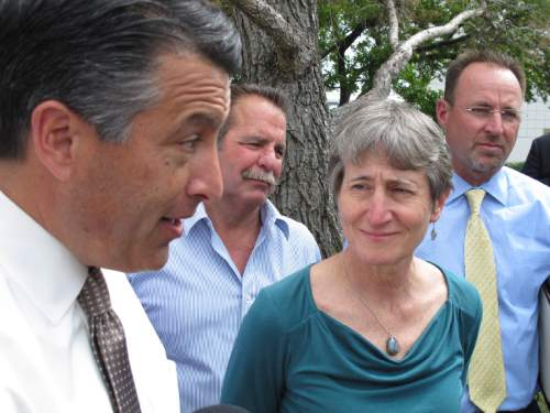 U.S. Interior Secretary Sally Jewell, right, looks on as Nevada Gov. Brian Sandoval, left, answers questions from reporters in Reno on Tuesday, April 21, 2015 after she announced her reversal of proposed federal protection of the bistate sage grouse along the California-Nevada line. Jewell says withdrawal of a proposal to declare the bird unique to Nevada and California as threatened should be encouraging for those trying to head off a bigger listing decision looming for greater sage grouse in 11 western states. (AP Photo/Scott Sonner)