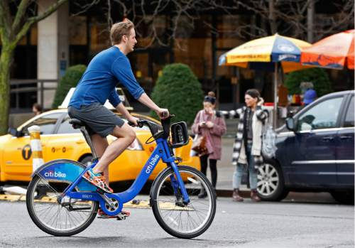 FILE - In this Dec. 24, 2015 file photo, a cyclist wearing shorts, sneakers and no socks, rides a rental bike through a downtown Manhattan street on Christmas Eve, in New York, as warm temperatures, rising into the 70's in New York.  Global warming has made the average daily weather for Americans more pleasant over the last 40 years, which may explain why much of the public doesn't rank climate change as big a threat as scientists and the rest of the world do, a new study suggests. (AP Photo/Kathy Willens, File)