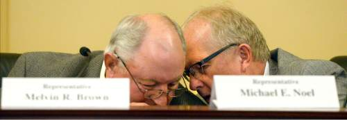 Al Hartmann  |  The Salt Lake Tribune Rep. Melvin Brown, R-Coalville, left, and Rep. Mike Noel, R-Kanab huddle in discussion as members of the Commission for the Stewardship of Public Lands debate revealing information from a law firm that would take Utah's case against the federal government in taking back federal land in the state.