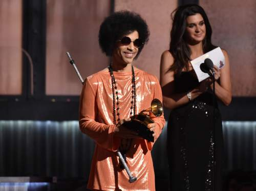 FILE - In this Feb. 8, 2015 file photo, Prince presents the award for album of the year at the 57th annual Grammy Awards in Los Angeles. Prince was the main attraction when he performed a concert early Saturday, Feb. 14, 2015 for a crowd that include Michael Jordan, Chris Rock, Questlove and Queen Latifah, who danced and sang to his rousing set in downtown New York City. (Photo by John Shearer/Invision/AP)