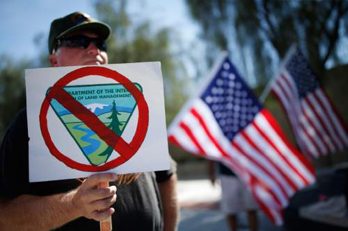 David Andersen, of Overton, Nev., holds a sign during a rally in support of rancher Cliven Bundy outside of the federal courthouse Friday, April 22, 2016, in Las Vegas. A U.S. magistrate judge is due to decide if trial will be held next month in Las Vegas for Bundy and 18 other defendants in an armed confrontation in Nevada with government agents two years ago.(AP Photo/John Locher)