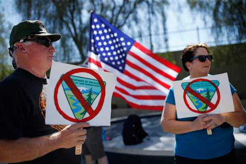 David Andersen, left, and Kaylene Andersen, of Overton, Nev., hold signs during a rally in support of rancher Cliven Bundy outside of the federal courthouse Friday, April 22, 2016, in Las Vegas. A U.S. magistrate judge is due to decide if trial will be held next month in Las Vegas for Bundy and 18 other defendants in an armed confrontation in Nevada with government agents two years ago.(AP Photo/John Locher)