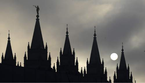 FILE - In this Feb. 6, 2013, file photo, the angel Moroni statue, silhouetted against a cloud-covered sky, sits atop the Salt Lake Temple, at Temple Square, in Salt Lake City. (AP Photo/Rick Bowmer, File)