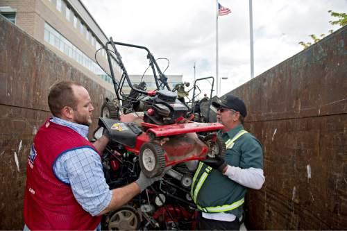 Lennie Mahler  |  The Salt Lake Tribune Jon Gordon and Ed Larrat load an old trade-in gas lawnmower into a dumpster as Lowe's and the DEQ offered new, environmentally friendly gas-powered lawnmowers at a discount during their CARROT program on Saturday.