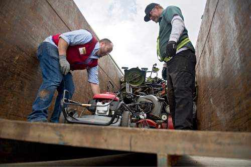 Lennie Mahler  |  The Salt Lake Tribune  Jon Gordon and Ed Larrat load old trade-in gas lawnmowers into a dumpster as Lowe's and the DEQ offered new, environmentally friendly gas-powered lawnmowers and trimmers at a discount during their CARROT program, Saturday, April 23, 2016.