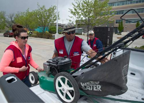 Lennie Mahler  |  The Salt Lake Tribune  Brooke Penner and Dino Pinder remove a customer's old trade-in gas lawnmower into a dumpster as the DEQ offered new, environmentally friendly gas-powered lawnmowers at a discount during their CARROT program, Saturday, April 23, 2016.