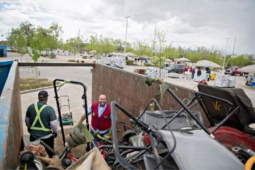 Lennie Mahler  |  The Salt Lake Tribune Jon Gordon and Ed Larrat load old trade-in gas lawnmowers into a dumpster as Lowe's on Saturday.