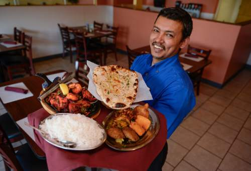Francisco Kjolseth   The Salt Lake Tribune  Bhim Shrestha, owner of Everest Curry Kitchen in Sandy, offers up some of his most popular dishes. Pictured are the Everest Tandoori Mix Grill, a combo of reshami kabab, chicken tikka, lamb chops, shrimp and chicken, chicken wings, garlic naan, and the Everest Platter, a mix of aloo tikki, paneer pakoda, vegetable pakoda and vegetable samosa.