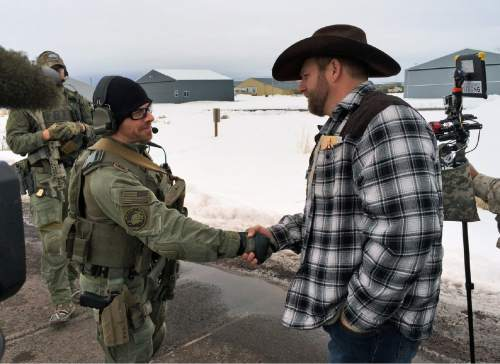 Ammon Bundy, right, shakes hand with a federal agent guarding the gate at the Burns Municipal Airport in Oregon on Friday, Jan. 22, 2016. Bundy is the leader of an armed group occupying a national wildlife refuge to protest federal land policies. (AP Photo/Keith Ridler).
