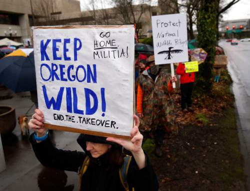 Renee Irvin holds a sign during a rally against the occupation of the Malheur National Wildlife Refuge by Ammon Bundy and his armed followers, while joining the rally at the Federal Building in Eugene, Ore., Tuesday, Jan. 19, 2016. With the armed takeover of the national wildlife refuge in southeastern Oregon in its third week, Bundy and his armed group are still trying to muster up broad community support, so far without much luck. (Andy Nelson/The Register-Guard via AP) MANDATORY CREDIT