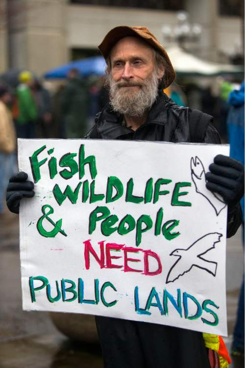 John Perry holds a poster during a rally against the occupation of the Malheur National Wildlife Refuge by Ammon Bundy and his armed followers, while joining the rally at the Federal Building in Eugene, Ore., Tuesday, Jan. 19, 2016. With the armed takeover of the national wildlife refuge in southeastern Oregon in its third week, Bundy and his armed group are still trying to muster up broad community support, so far without much luck. (Andy Nelson/The Register-Guard via AP) MANDATORY CREDIT