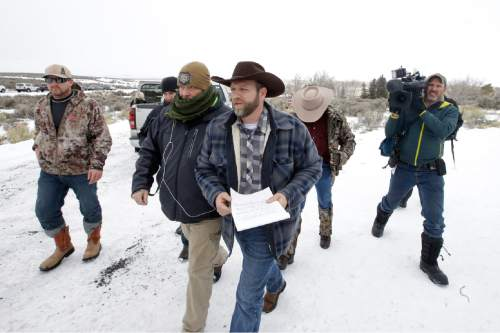 Ammon Bundy, center, one of the sons of Nevada rancher Cliven Bundy, arrives for a news conference at Malheur National Wildlife Refuge Tuesday, Jan. 5, 2016, near Burns, Ore. Law enforcement had yet to take any action Tuesday against a group numbering close to two dozen, led by Bundy and his brother, who are upset over federal land policy. (AP Photo/Rick Bowmer)