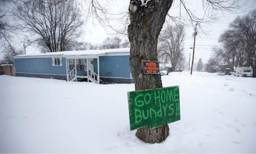A sign referencing Ammon Bundy and his brother, who are the sons of Nevada rancher Cliven Bundy, hangs on a tree in front of a home Tuesday, Jan. 5, 2016, in Burns, Ore. Ammon Bundy, the leader of a small, armed group that is occupying a remote national wildlife preserve in Oregon said Tuesday that they will go home when a plan is in place to turn over management of federal lands to locals. (AP Photo/Rick Bowmer)