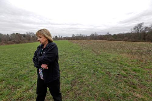"In this April 12, 2016 photo, Desiree Moninski, walks on land located across from her house in Dudley, Mass., which is the site of a proposed Muslim cemetery, a project vigorously opposed by area residents. Regarding the land once farmed by her grandparents, Moninski said she and other opponents have legitimate concerns that have nothing to do with Islam. ""I grew up here. It's farmland, and I'd like to see it stay that way,"" she said. (AP Photo/Elise Amendola)"